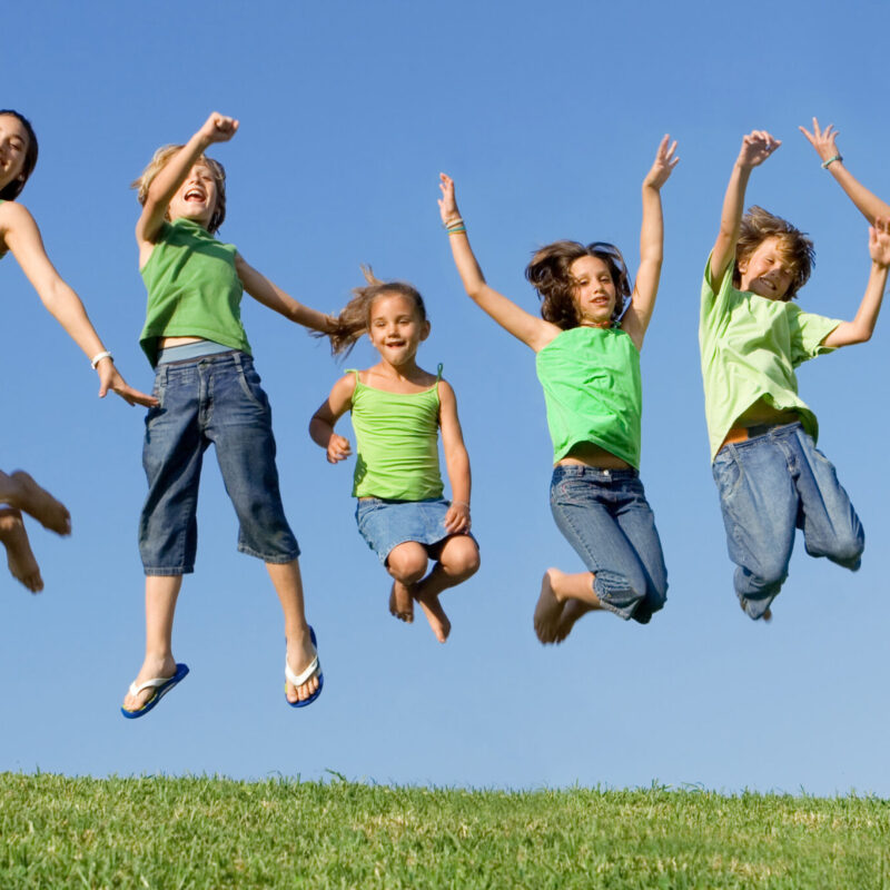 happy healthy smiling group of kids children jumping for joy at summer camp